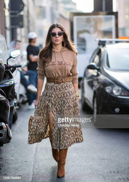 A guest wearing hoody and skirt with slit and snake print is seen outside Max Mara during Milan Fashion Week Spring/Summer 2019 on September 20 2018...