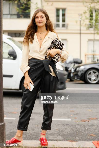 A guest wearing ivory shirt black leather pants and red flats outside Loewe during Paris Fashion Week Womenswear Spring Summer 2020 on September 27...