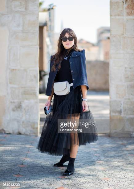 A guest wearing jacket with strong shoulder belt bag sheer dress is seen during Tel Aviv Fashion Week on March 12 2018 in Tel Aviv Israel