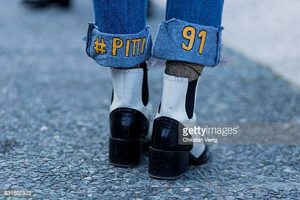 A guest wearing jeans with the print Pitti Uomo 91 on January 11 2017 in Florence Italy