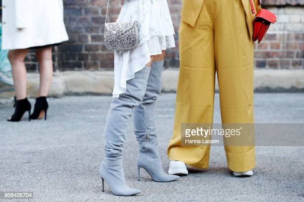 A guest wearing knee high boots and Xaviar clutch during MercedesBenz Fashion Week Resort 19 Collections at Carriageworks on May 17 2018 in Sydney...