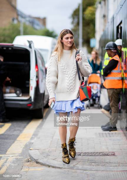 A guest wearing knit blue mini skirt snake print boots multi colored Loewe bag is seen outside Natasha Zinko during London Fashion Week September...
