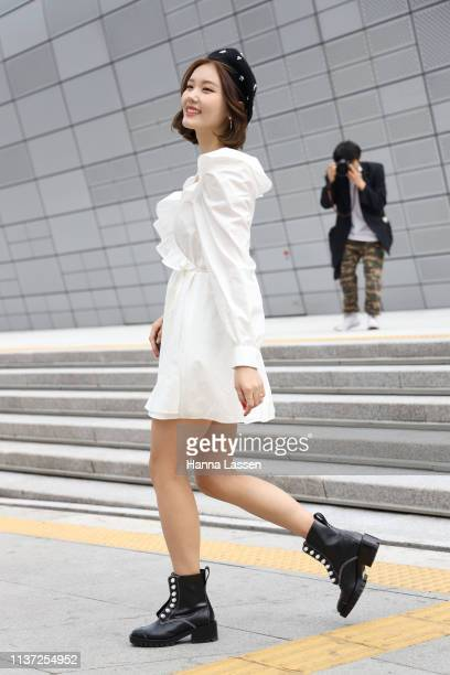 Guest wearing leather jacket white mini dress black beret ankle leather boots and Yves Saint Laurent clutch is seen at the Hera Seoul Fashion Week...