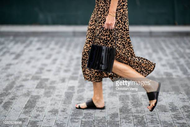 Guest wearing leopard dress, black bag, sandals is seen outside Michael Kors during New York Fashion Week Spring/Summer 2019 on September 12, 2018 in...