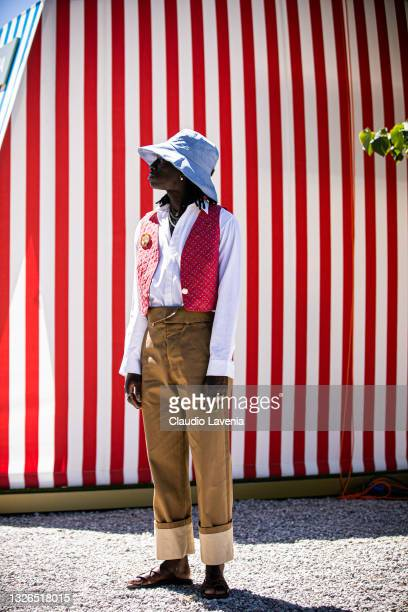 Guest, wearing light blue cap, white shirt, brown pants and red gilet, is seen at Fortezza Da Basso on July 01, 2021 in Florence, Italy.