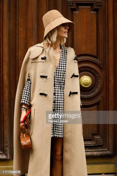 Guest wearing light brown bucket hat, black mini dress outside Lanvin on September 25, 2019 in Paris, France.