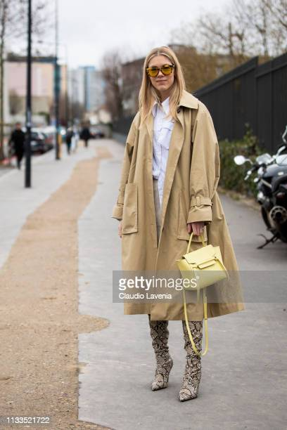 A guest wearing long beige trench coat snake print boots and light yellow bag is seen outside Balenciaga on Day 7 Paris Fashion Week Autumn/Winter...