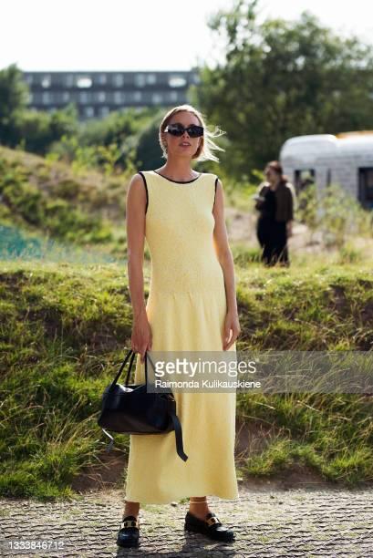 Guest wearing long yellow dress outside Ganni during Copenhagen fashion week SS22 on August 12, 2021 in Copenhagen, Denmark.
