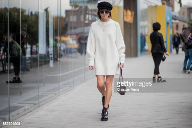 A guest wearing military har white wide knit worn as a dress boots Chanel bag sunglasses is seen during Tbilisi Fashion Week Spring/Summer 2018 on...