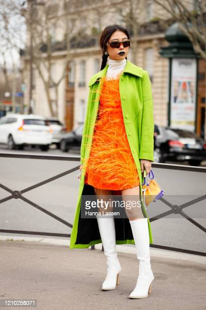 Guest wearing Miu Miu neon green coat, orange feather dress and white leather boots outside the Miu Miu show during Paris Fashion Week Womenswear...