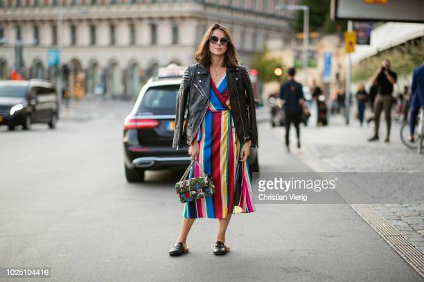 A guest wearing multi color striped dress leather jacket bag Gucci slippers is seen during Stockholm Runway SS19 on August 29 2018 in Stockholm Sweden