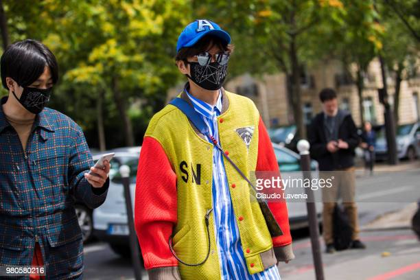 A guest wearing multicolored bomber jacket and Louis Vuitton bag is seen in the streets of Paris before the Rick Owens show during Paris Men's...