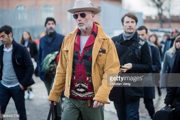 A guest wearing mustard jacket hat cardigan is seen during the 93 Pitti Immagine Uomo at Fortezza Da Basso on January 10 2018 in Florence Italy