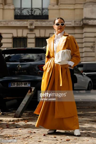 Guest wearing mustard leather coat and a white Bottega Veneta clutch outside the Elie Saab show during Womenswear Spring/Summer 2020 show Paris...