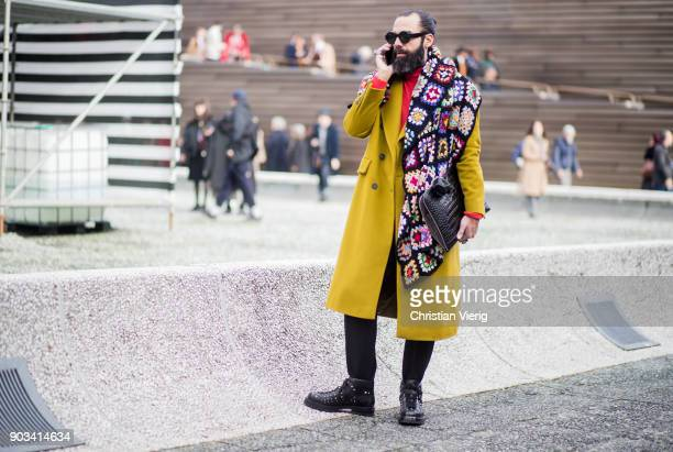 A guest wearing mustard wool coat clutch scarf with flower print is seen during the 93 Pitti Immagine Uomo at Fortezza Da Basso on January 10 2018 in...