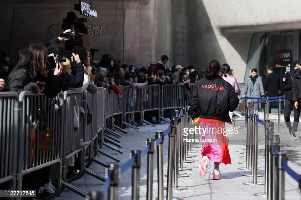 Guest wearing Naomi Ave bomber jacket neon pink skirt and baby pink sneakers is seen at the Hera Seoul Fashion Week 2019 F/W at Dongdaemun Design...