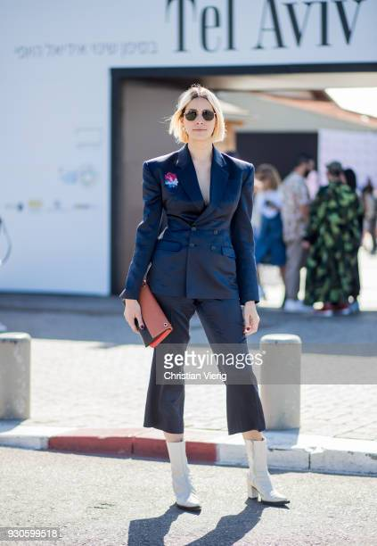 A guest wearing navy blazer navy cropped pants white ankle boots is seen during Tel Aviv Fashion Week on March 11 2018 in Tel Aviv Israel