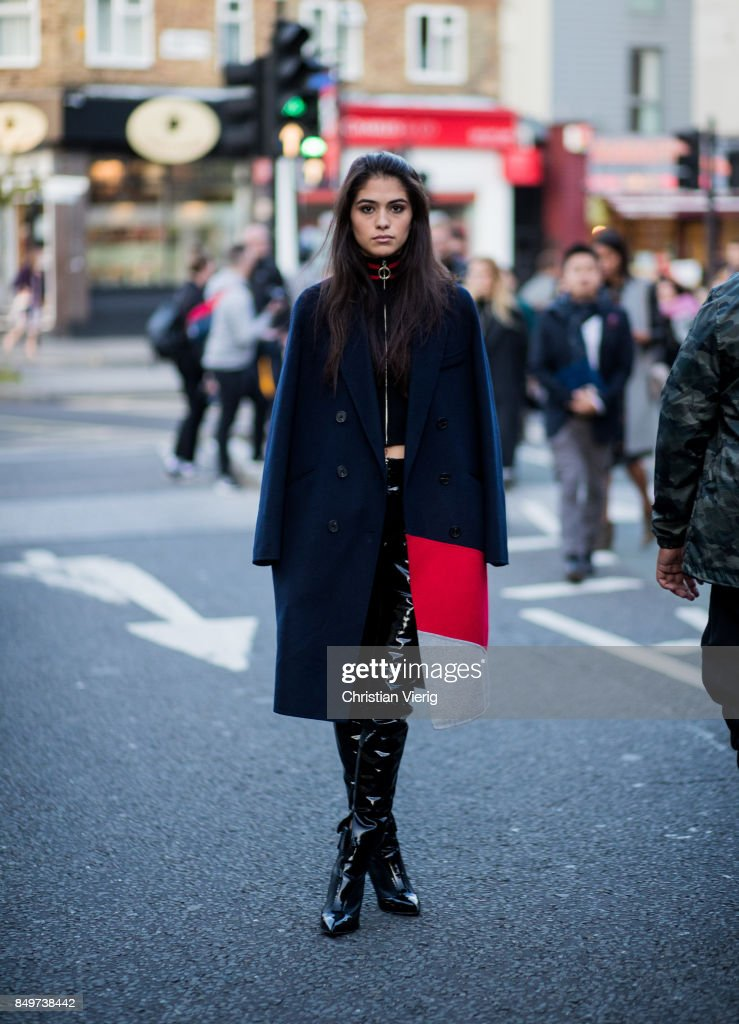 A guest wearing navy blue cape outside Tommy Hilfiger during London Fashion Week September 2017 on September 19, 2017 in London, England.
