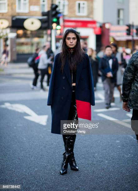 A guest wearing navy blue cape outside Tommy Hilfiger during London Fashion Week September 2017 on September 19 2017 in London England
