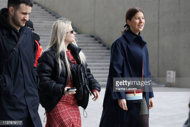 Guest wearing navy trench coat and red white blue and black colourblocked mini bag is seen at the Hera Seoul Fashion Week 2019 F/W at Dongdaemun...