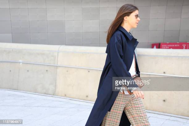 Guest wearing navy trench plaid pants and brown leather bag is seen at the Seoul Fashion Week 2019 F/W at Dongdaemun Design Plaza at Dongdaemun...
