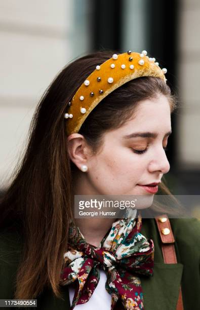 Guest wearing neck tie and oversized mustard yellow Aliceband headband with pearls is seen during New York Fashion Week on September 09, 2019 in New...
