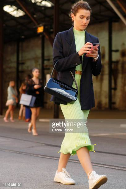 A guest wearing neon green twopiece navy jacket and white sneakers at MercedesBenz Fashion Week Resort 20 Collections on May 15 2019 in Sydney...