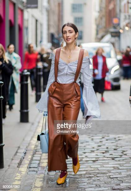 A guest wearing off shoulder button shirt brown overall seen outside Preen during London Fashion Week February 2018 on February 18 2018 in London...