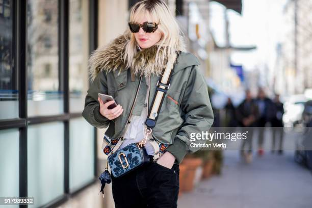 A guest wearing olive bomber jacket seen outside Gabriela Hearst on February 13 2018 in New York City