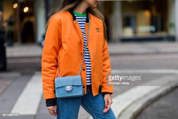 A guest wearing orange Adidas bomber jacket baby blue Chanel bag denim jeans on August 31 2017 in Stockholm Sweden