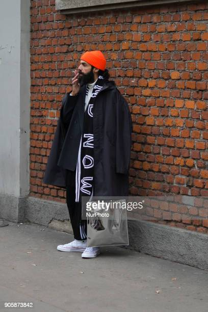 A guest wearing orange beanie black white scarf grey blazer jacket black jacket is seen outside No21 during Milan Men's Fashion Week Fall/Winter...