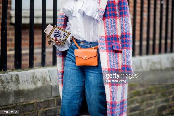 A guest wearing orange belt bag seen outside Temperley London during London Fashion Week February 2018 on February 18 2018 in London England
