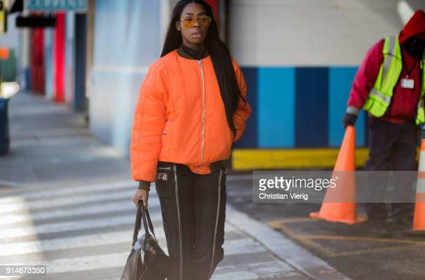 A guest wearing orange bomber jacket is seen during Mens' New York Fashion Week on February 5 2018 in New York City