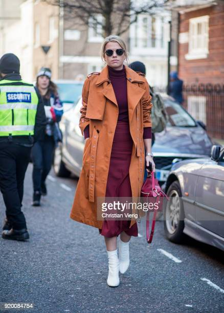 A guest wearing orange brown trench coat bordeaux turtleneck skirt white boots seen outside Temperley London during London Fashion Week February 2018...