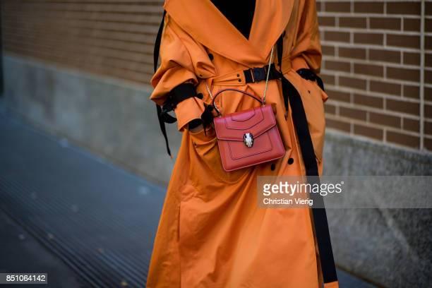 A guest wearing orange coat Bvlgari bag is seen outside Fendi during Milan Fashion Week Spring/Summer 2018 on September 21 2017 in Milan Italy