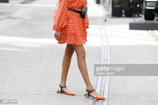 A guest wearing orange dress with bum bag during MercedesBenz Fashion Week Resort 19 Collections at Carriageworks on May 16 2018 in Sydney Australia