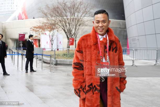 Guest wearing orange faux fur coat Gucci belt wine burgundy pants and black leather shoes is seen at the Hera Seoul Fashion Week 2019 F/W at...