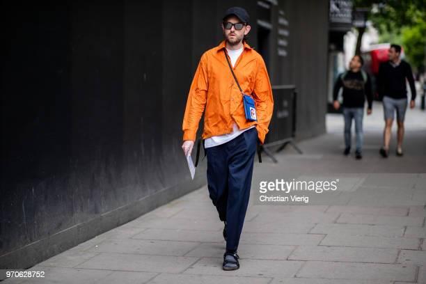 A guest wearing orange jacket navy pants Prada mini bag cap sandals is seen during London Fashion Week Men's June 2018 on June 9 2018 in London...