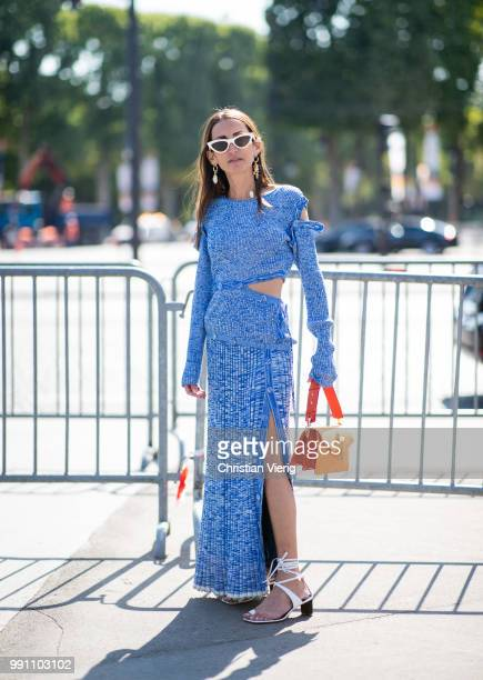A guest wearing orange JW Anderson bag and blue dress with slit seen outside Chanel on day three during Paris Fashion Week Haute Couture FW18 on July...