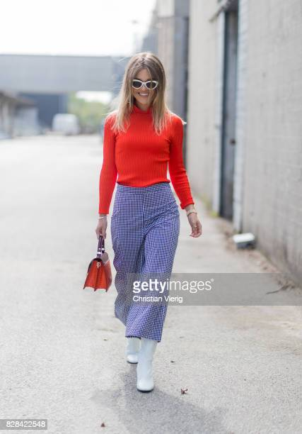 A guest wearing orange knit cropped pants white boots outside By Malene Birger on August 09 2017 in Copenhagen Denmark