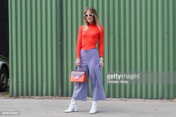A guest wearing orange knit cropped pants white boots outside By Malene Birger on August 09 2017 in Copenhagen Denmark
