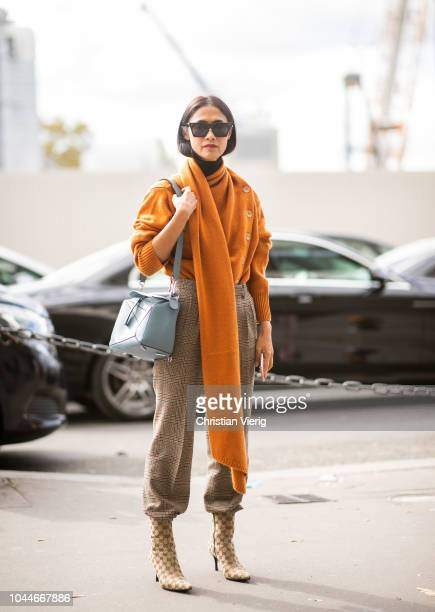 A guest wearing orange knit cropped plaid pants Gucci ankle boots blue Loewe bag is seen outside Giambattista Valli during Paris Fashion Week...