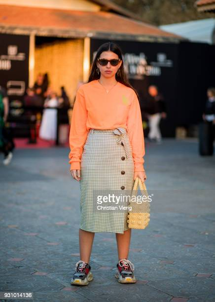 A guest wearing orange knit skirt Balenciaga sneaker bag is seen during Tel Aviv Fashion Week on March 12 2018 in Tel Aviv Israel