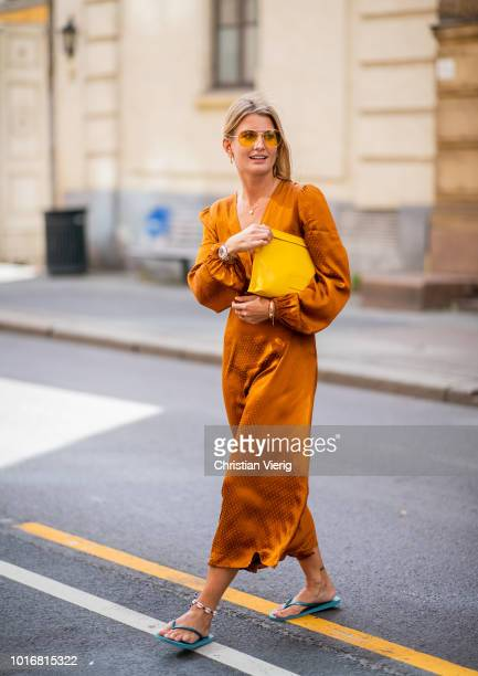 A guest wearing orange silk dress yellow clutch is seen outside Epilogue during Oslo Runway SS19 on August 14 2018 in Oslo Norway