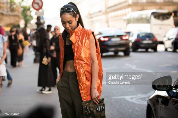 A guest wearing orange sleeveless jacket green pants and Valentino camouflage hand bag is seen in the streets of Paris after the Valentino show...