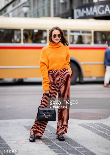 A guest wearing orange turtleneck high waist pants is seen outside Pia Tjelta during Oslo Runway SS19 on August 15 2018 in Oslo Norway