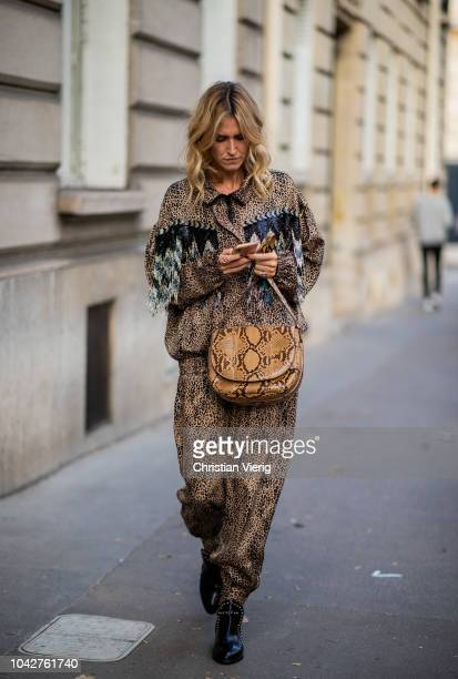 A guest wearing overall and bag with snake print is seen outside Alessandra Rich during Paris Fashion Week Womenswear Spring/Summer 2019 on September...