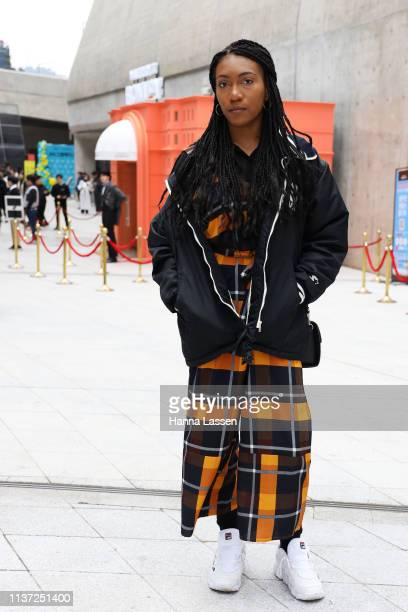 Guest wearing oversized black zipup jacket and orange check maxi dress with Fila sneakers is seen at the Hera Seoul Fashion Week 2019 F/W at...