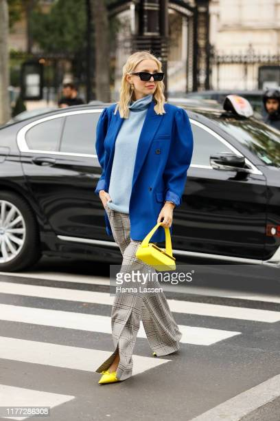 Guest wearing oversized blue blazer, split check pants, yellow Victoria Beckham clutch and Balenciaga mules outside Paco Rabanne during Paris Fashion...