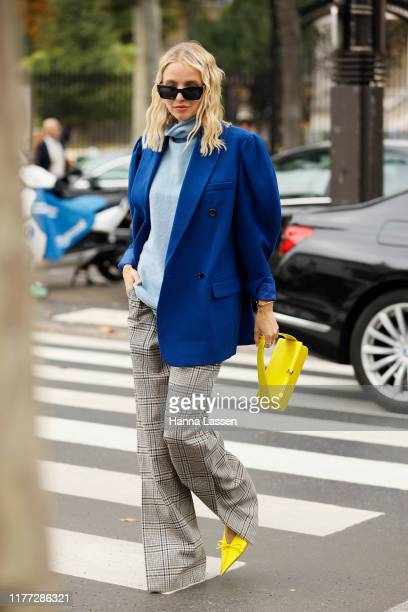 A guest wearing oversized blue blazer split check pants yellow Victoria Beckham clutch and Balenciaga mules outside Paco Rabanne during Paris Fashion...